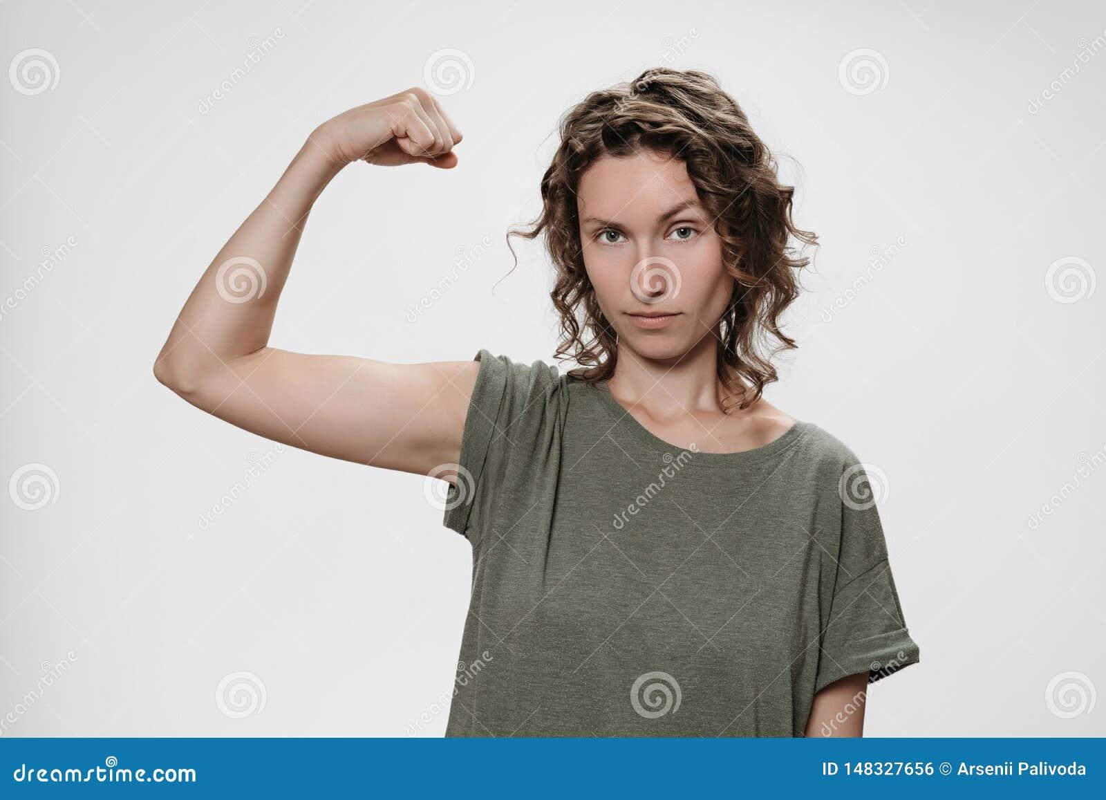 La mujer joven del pelo rizado muestra el m?sculo en su mano, siente orgullosa ser fuerte