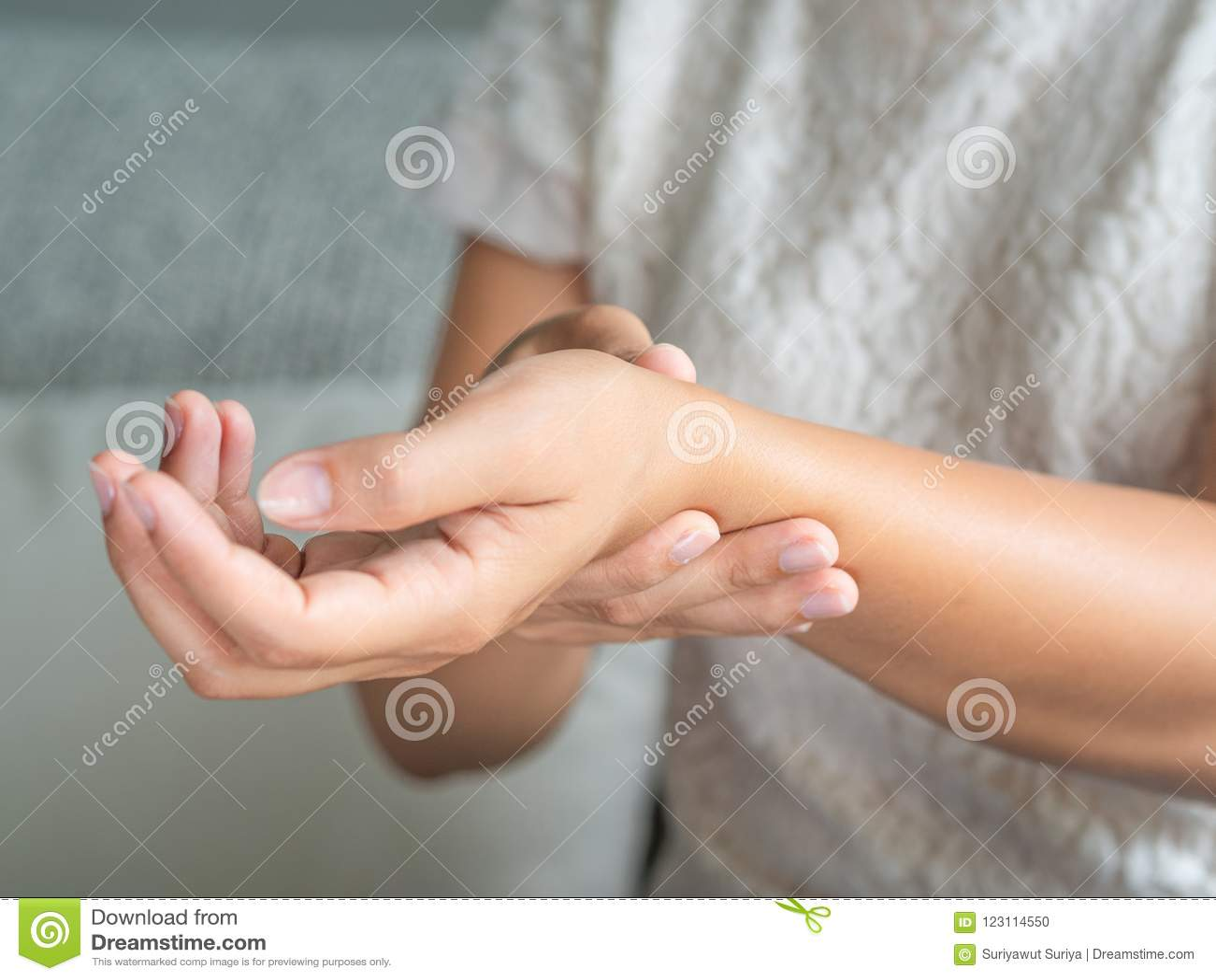 La mujer joven del primer que se sienta en el sofá lleva a cabo su lesión de mano de la muñeca