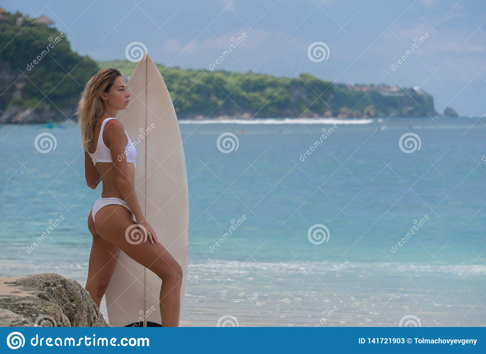 La mujer joven delgada se coloca de lado a la cámara, tablero de la tenencia, listo para practicar surf