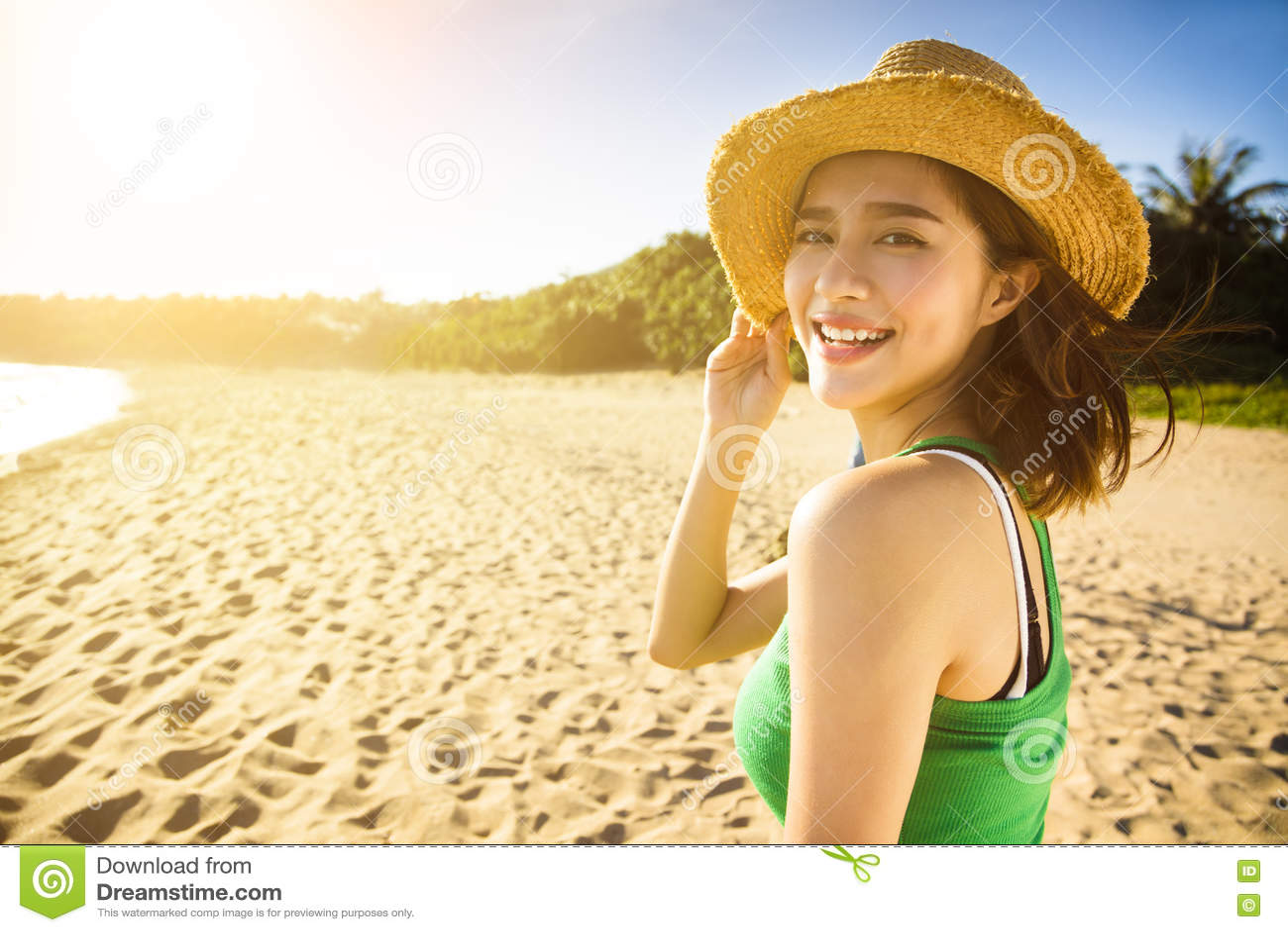 La mujer joven disfruta de vacaciones de verano en la playa