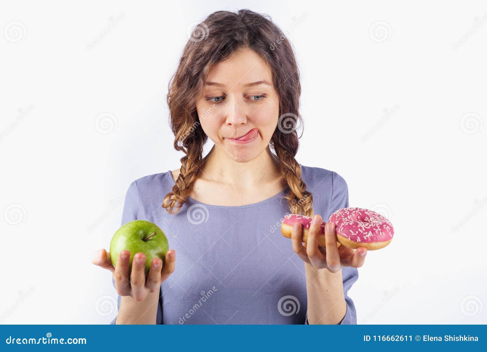 La mujer joven elige entre un buñuelo y una manzana, muchacha lame la boca Concepto de nutrición y de dieta dañinas