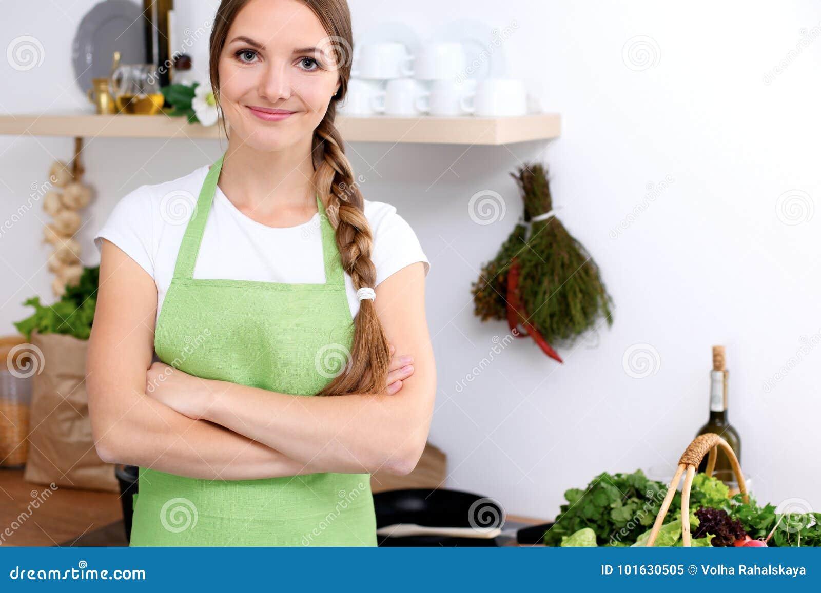 La mujer joven en delantal verde va para cocinar en una cocina El ama de casa está probando la sopa al lado de la cuchara de made