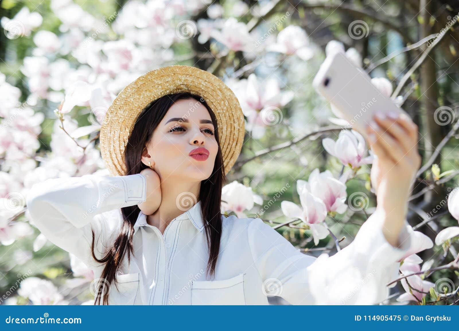 4559ae1a87 La mujer joven en gafas de sol y el sombrero de paja toman el selfie en el  teléfono para la red social rodeada con la magnolia Estación de resorte