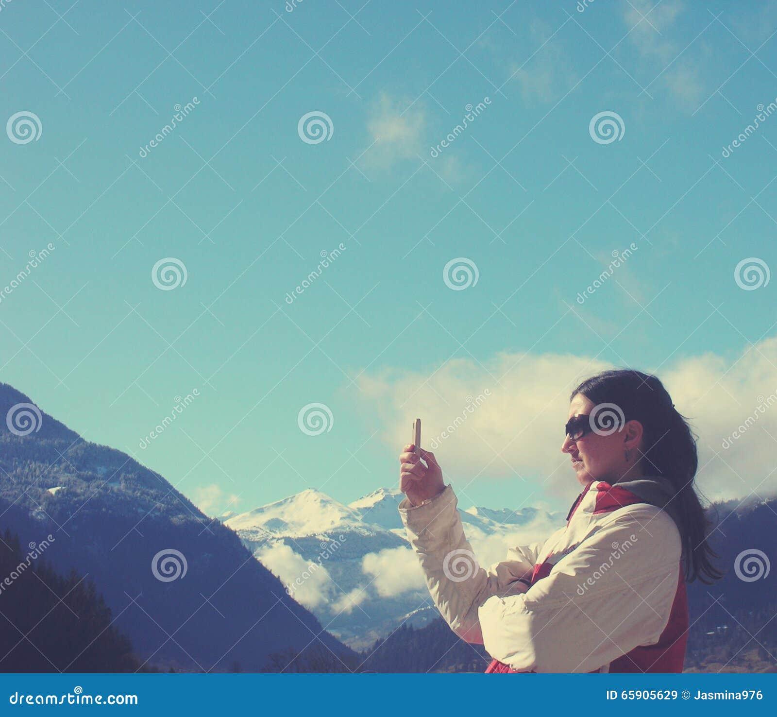 La mujer joven en invierno viste mandar un SMS en el teléfono móvil; estilo retro