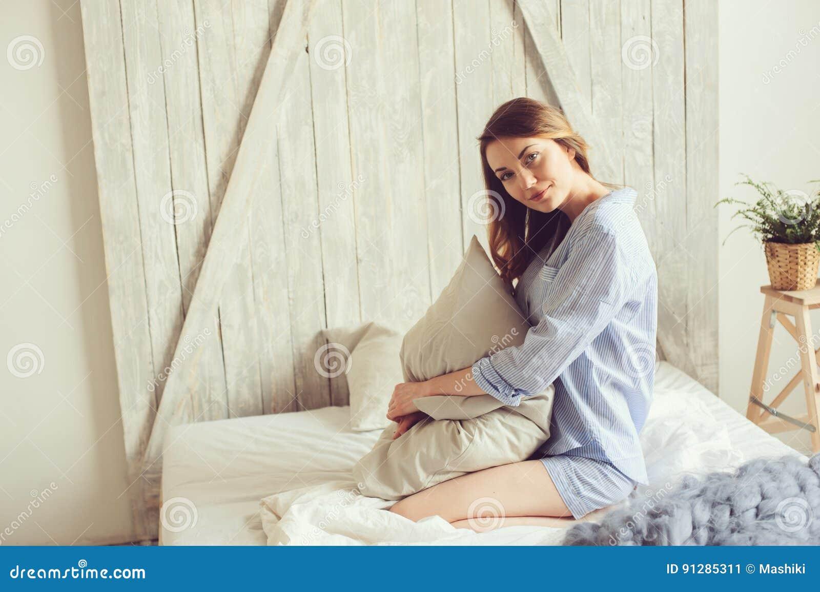 af5306e223 La mujer joven en pijama despierta por la mañana en dormitorio escandinavo  acogedor y la mentira en cama con la manta hecha punto de gran tamaño Forma  de ...