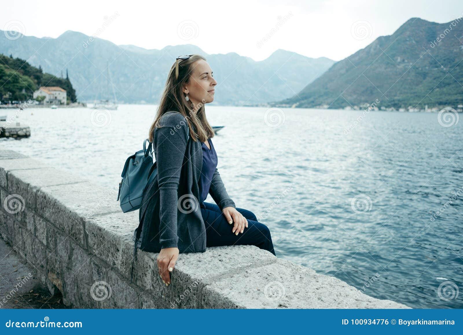 La mujer joven en rebeca gris y mochila azul se sienta cerca del mar