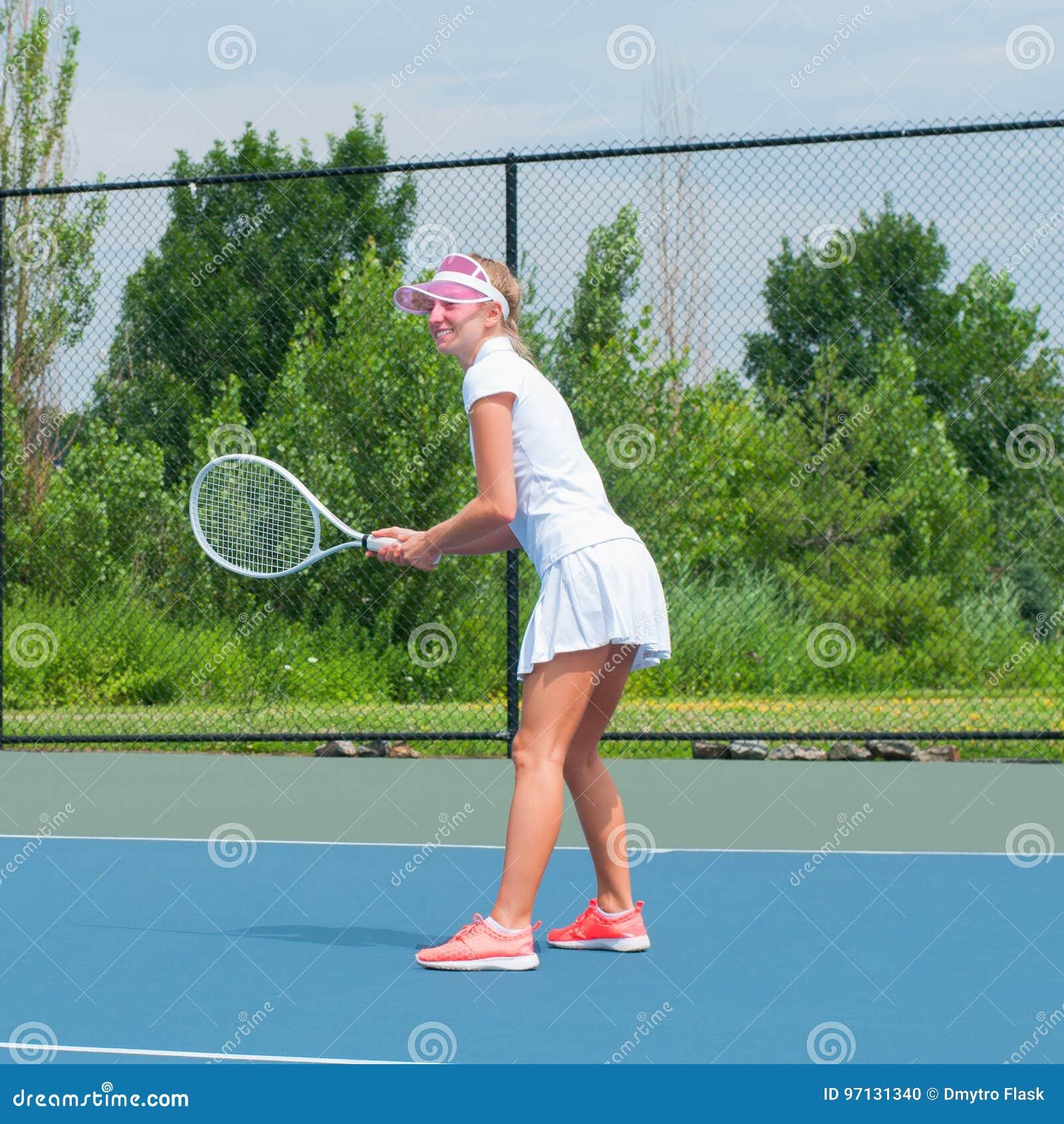 fbc3bf0be8 La mujer joven está jugando a tenis en el campo de tenis en un día soleado  hermoso