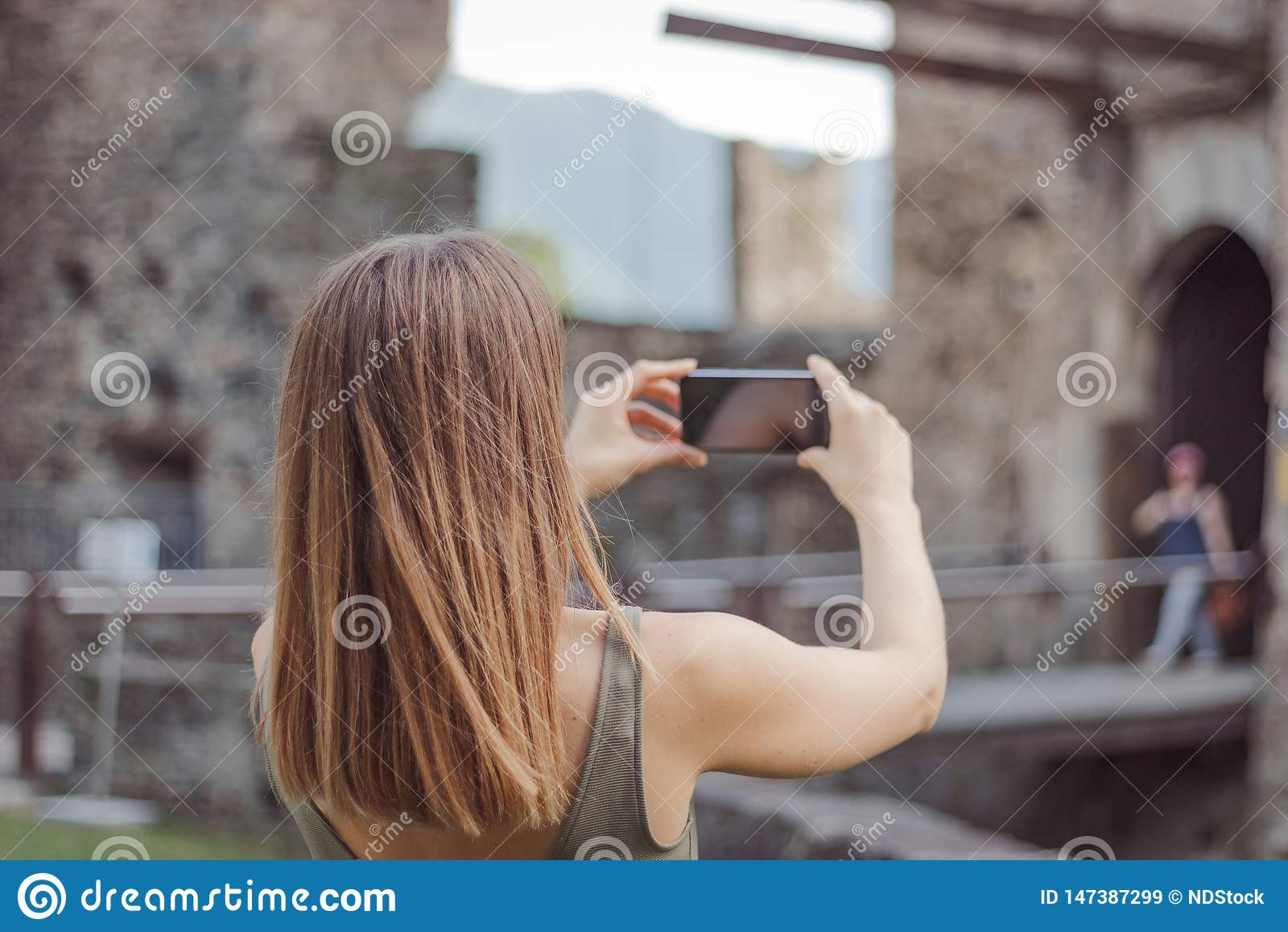 La mujer joven está tomando una imagen de un castillo