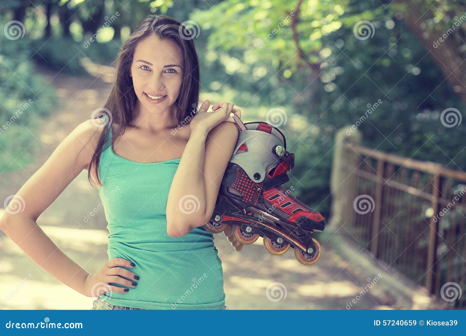 La mujer joven feliz del retrato que va rollerblading sostenerse en línea patina