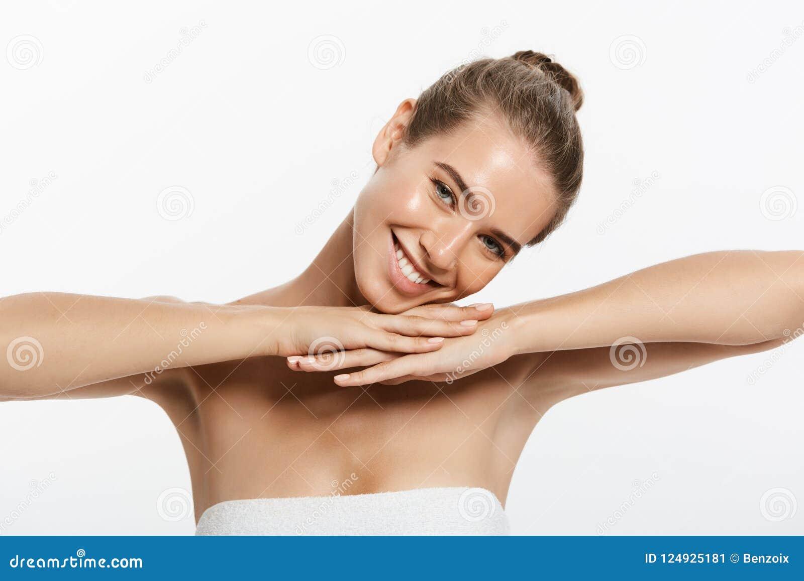 La mujer joven hermosa con tacto fresco limpio de la piel posee la cara Tratamiento facial Cosmetología, belleza y balneario