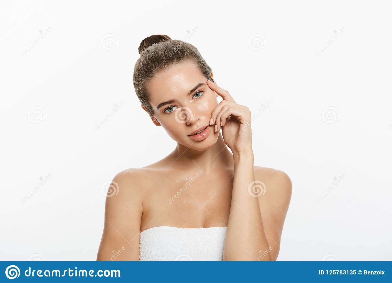 La mujer joven hermosa con tacto fresco limpio de la piel posee la cara Tratamiento facial Cosmetología, belleza y balneario Aisl