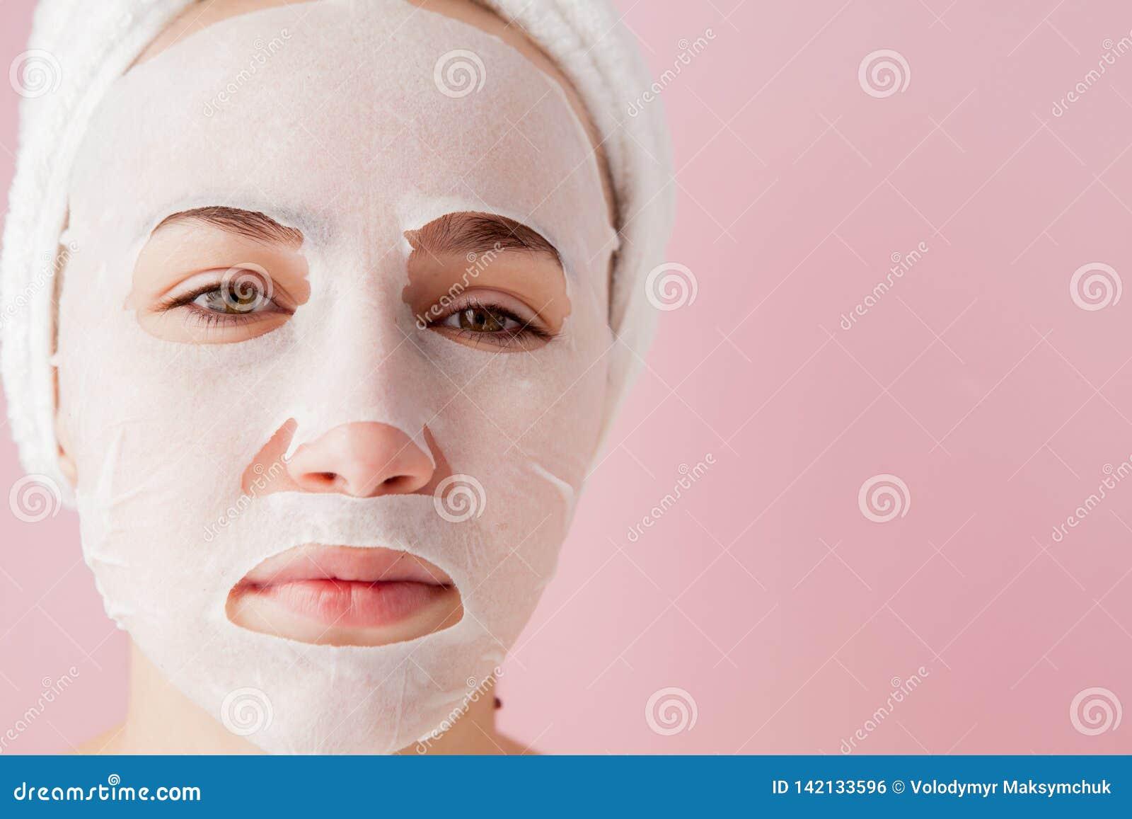 La mujer joven hermosa está aplicando una máscara cosmética del tejido en una cara en un fondo rosado Tratamiento de la atención