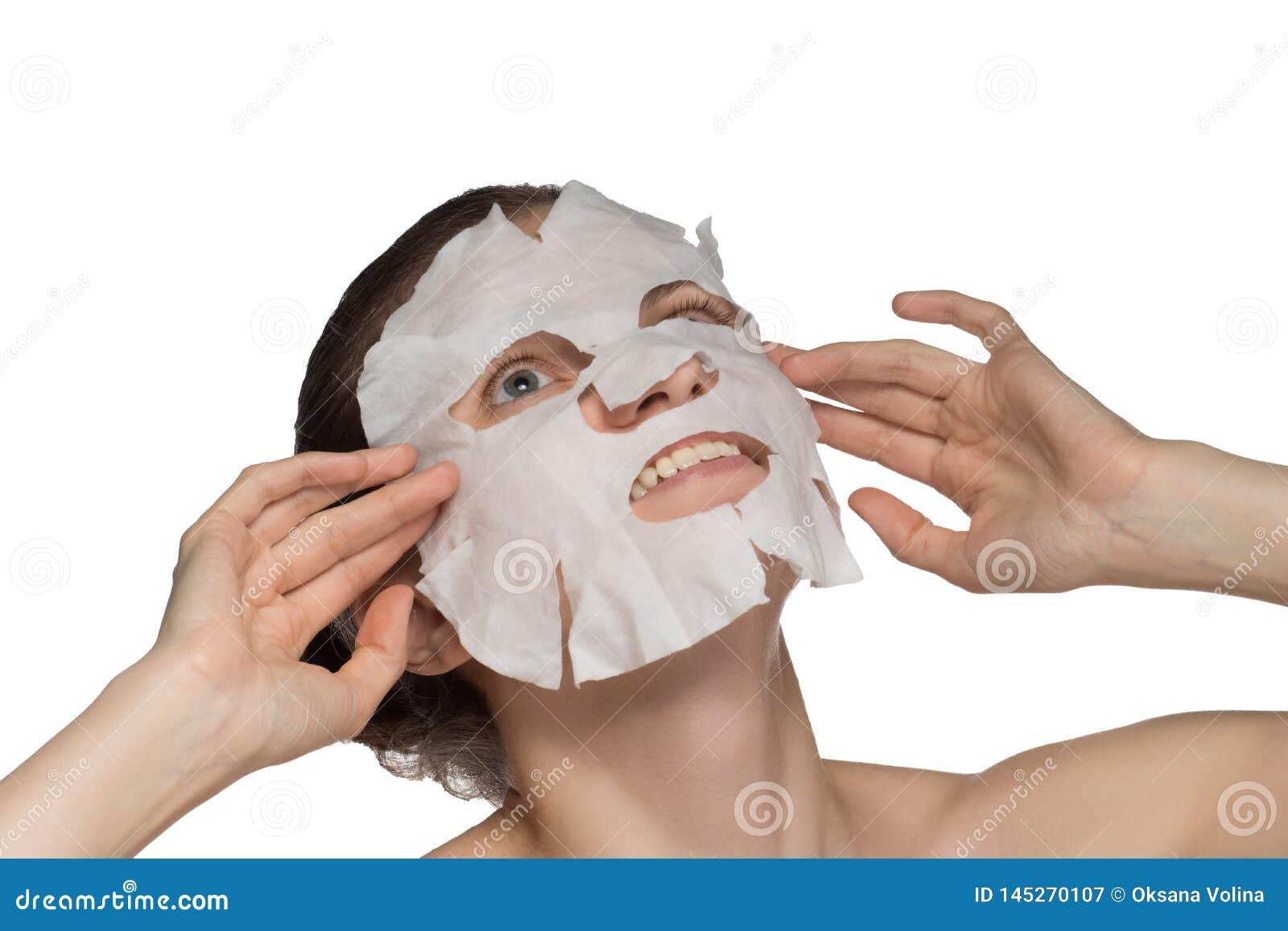 La mujer joven hermosa est? aplicando una m?scara cosm?tica en una cara en un fondo blanco