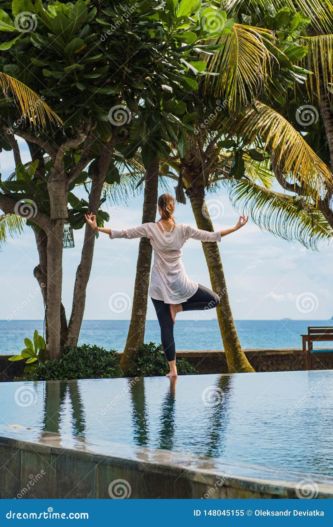 La mujer joven hermosa está practicando la yoga, meditación, colocando actitud en una pierna en la piscina con el paisaje del océ