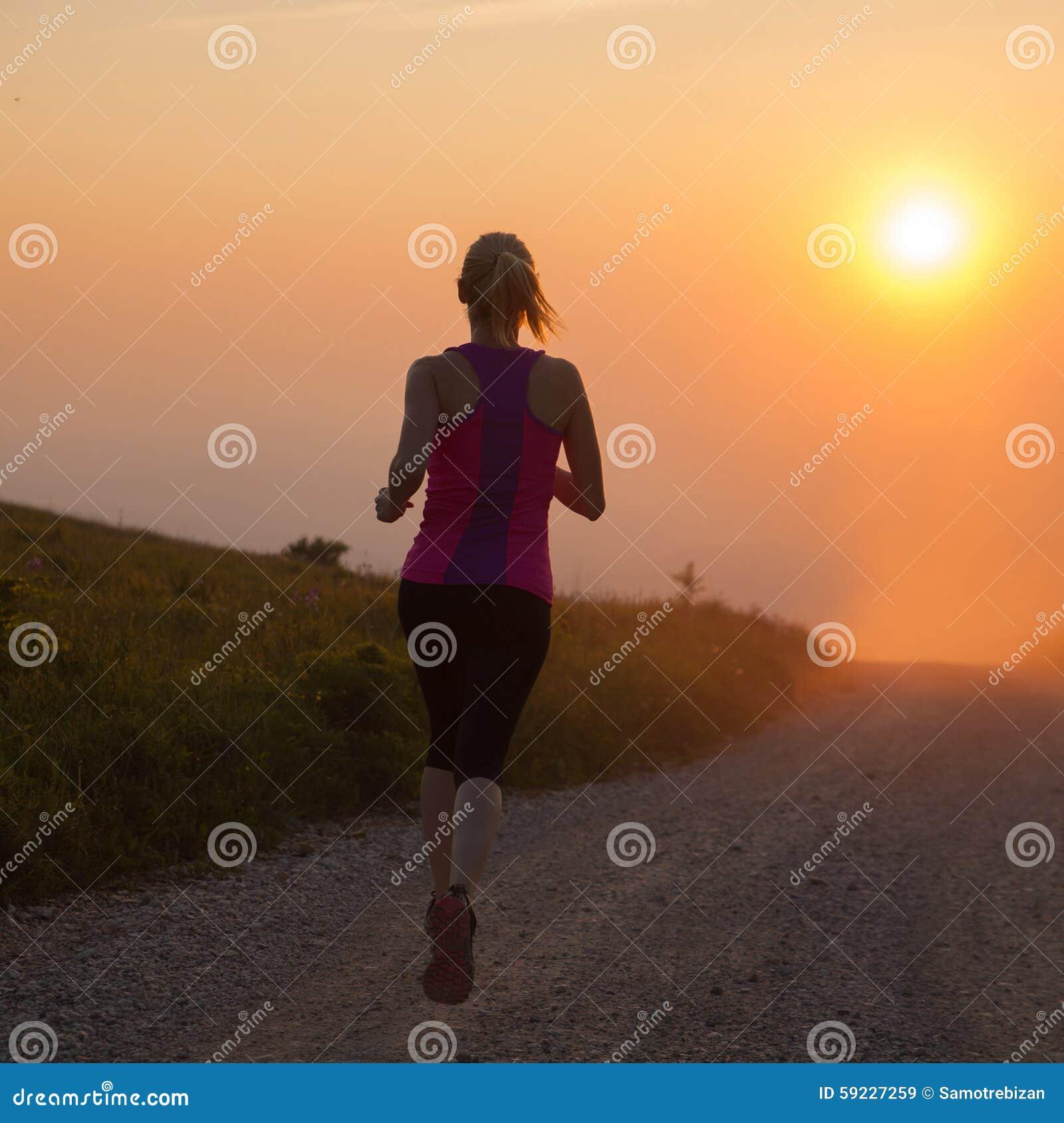 La mujer joven hermosa funciona con el campo a través en una trayectoria de la montaña
