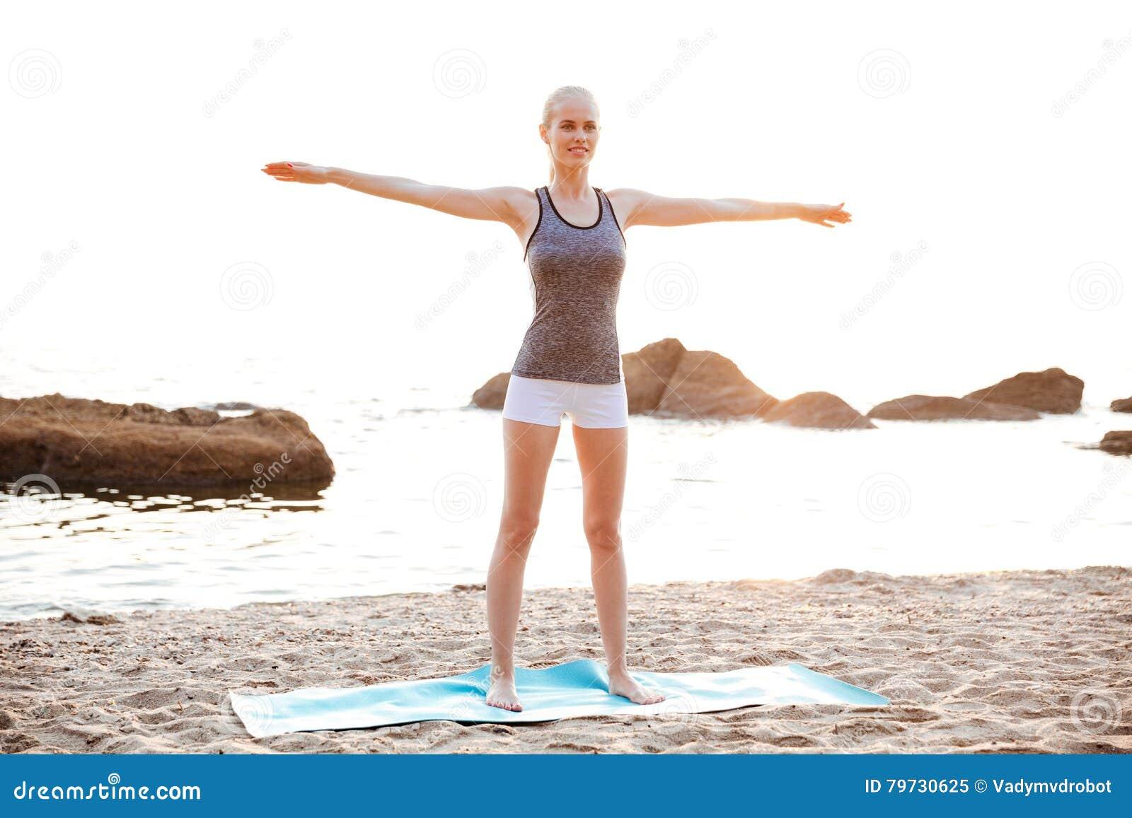 La mujer joven hermosa que hace estirar ejercita durante yoga