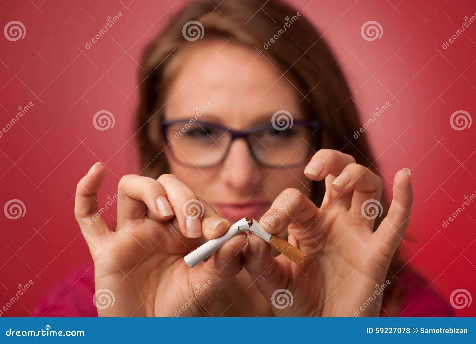 La mujer joven hermosa rompe un cigarrillo como gesto para s abandonado