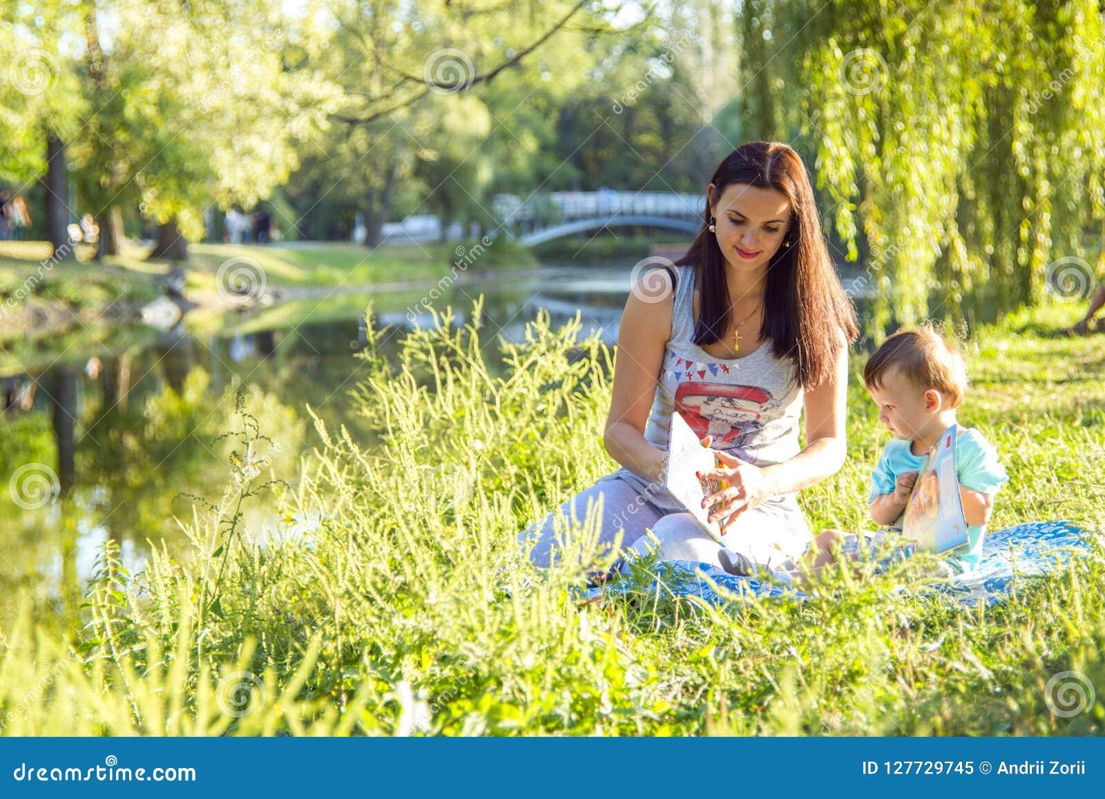 La mujer joven hermosa y su pequeño hijo adorable juegan en parque soleado, leyeron los libros