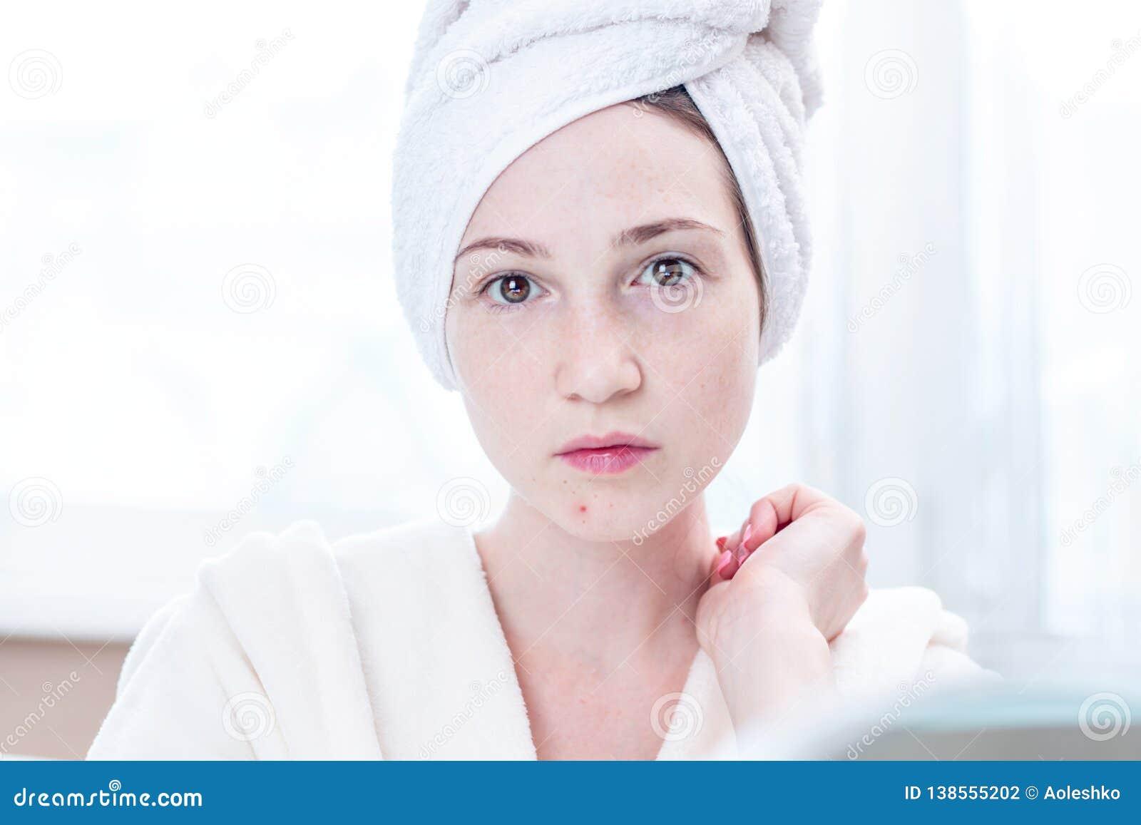 La mujer joven infeliz hermosa detecta acné en su cara Concepto de higiene y de cuidado para la piel