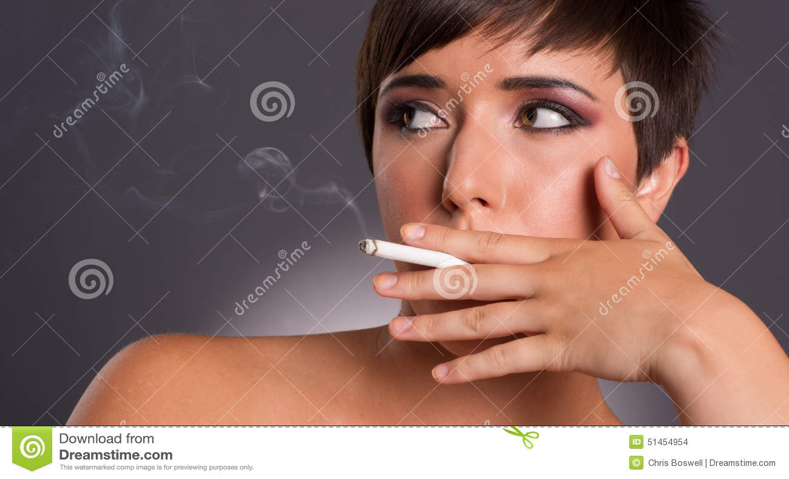 La mujer joven inhala el retrato íntimo del fumador del humo del cigarrillo
