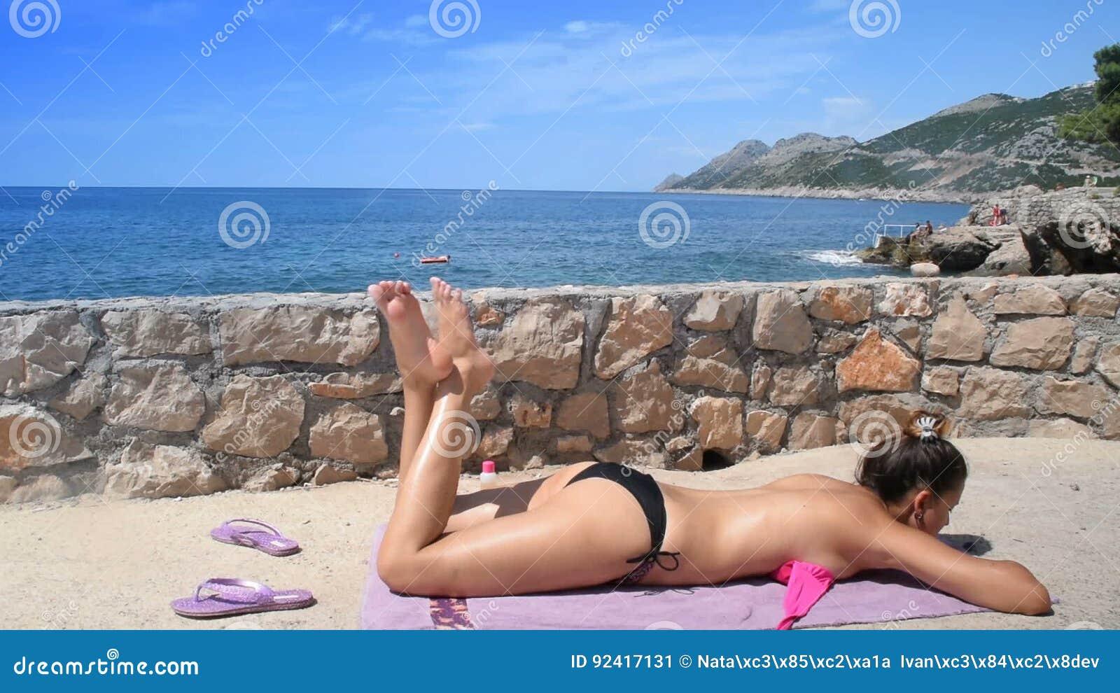 La Mujer Joven Muchacha Femenina En Un Bañador Está Tomando El Sol