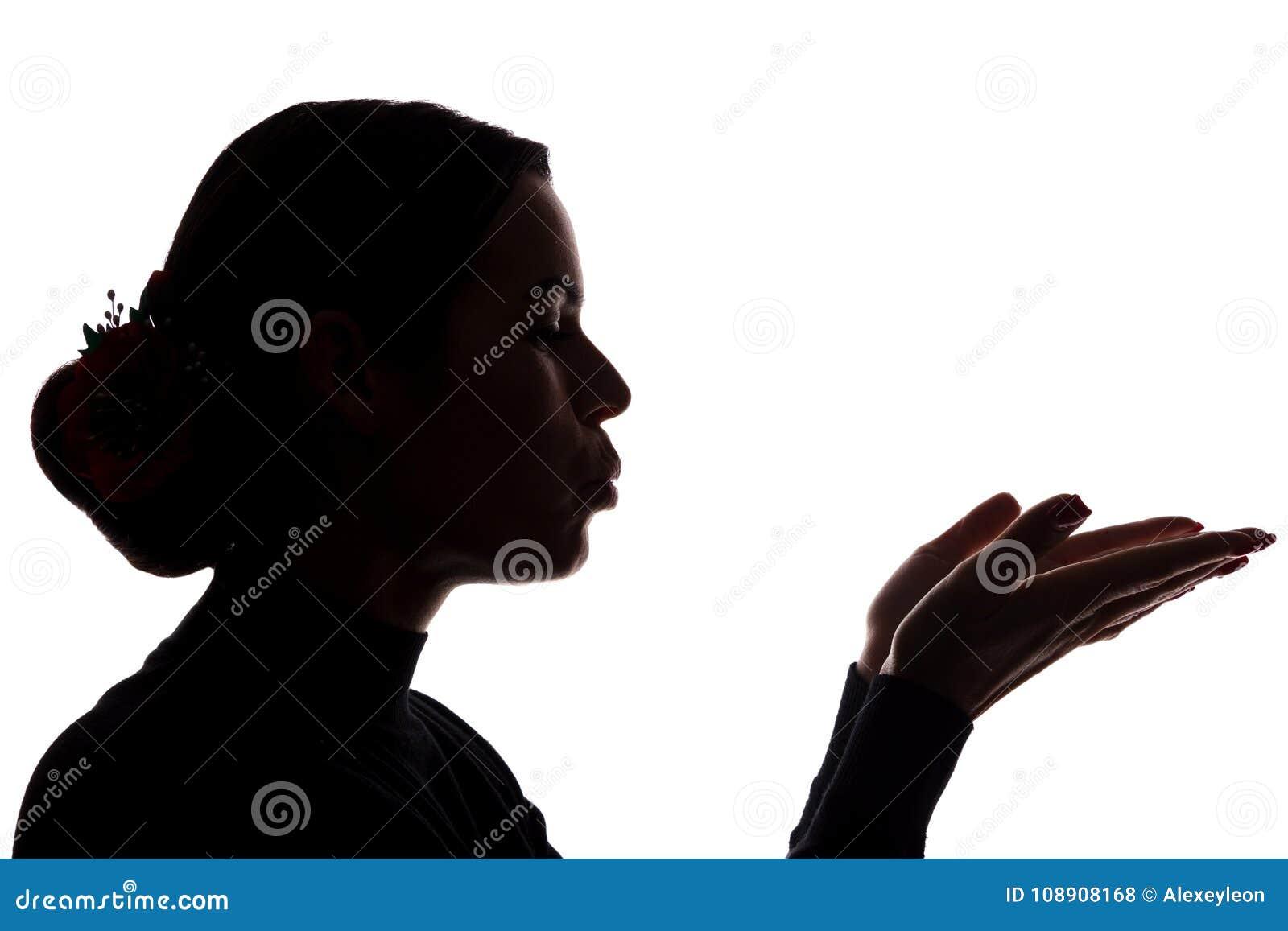 La mujer joven muestra sus manos delanteras, enviando un beso