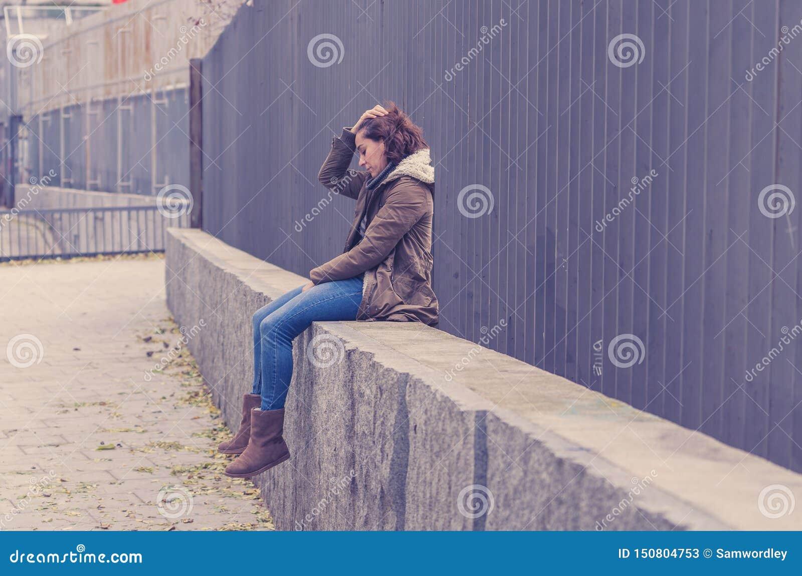 La mujer joven presionada que se sentaba en la calle urbana de la ciudad abrum? a