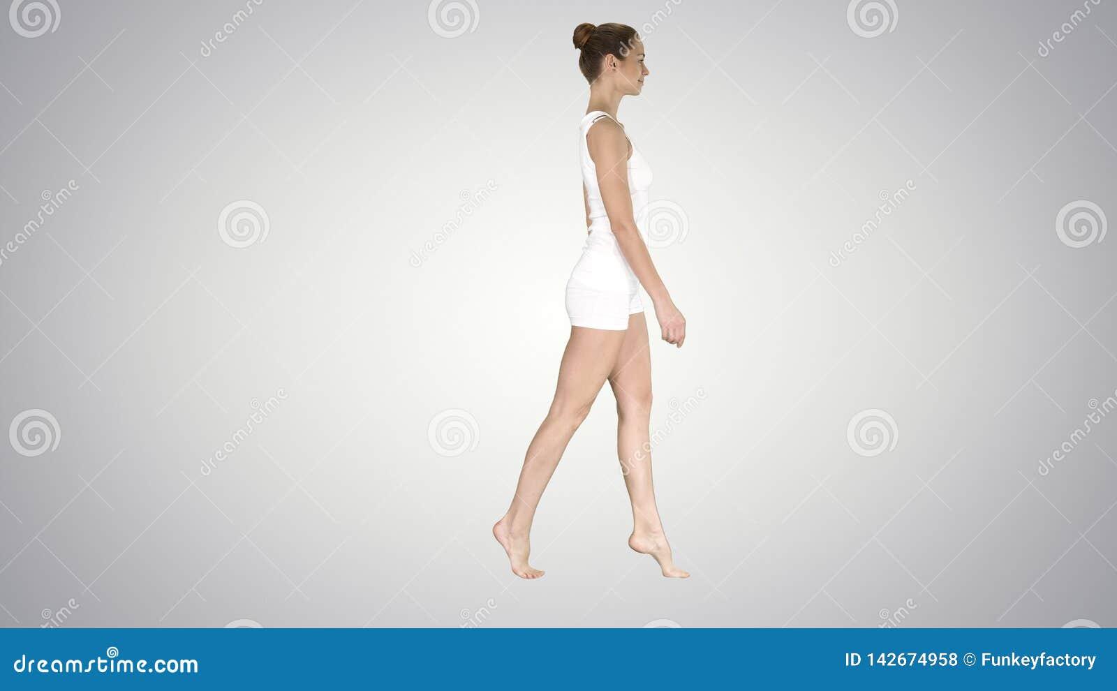 La mujer joven que camina en sus puntas del pie en fondo de la pendiente
