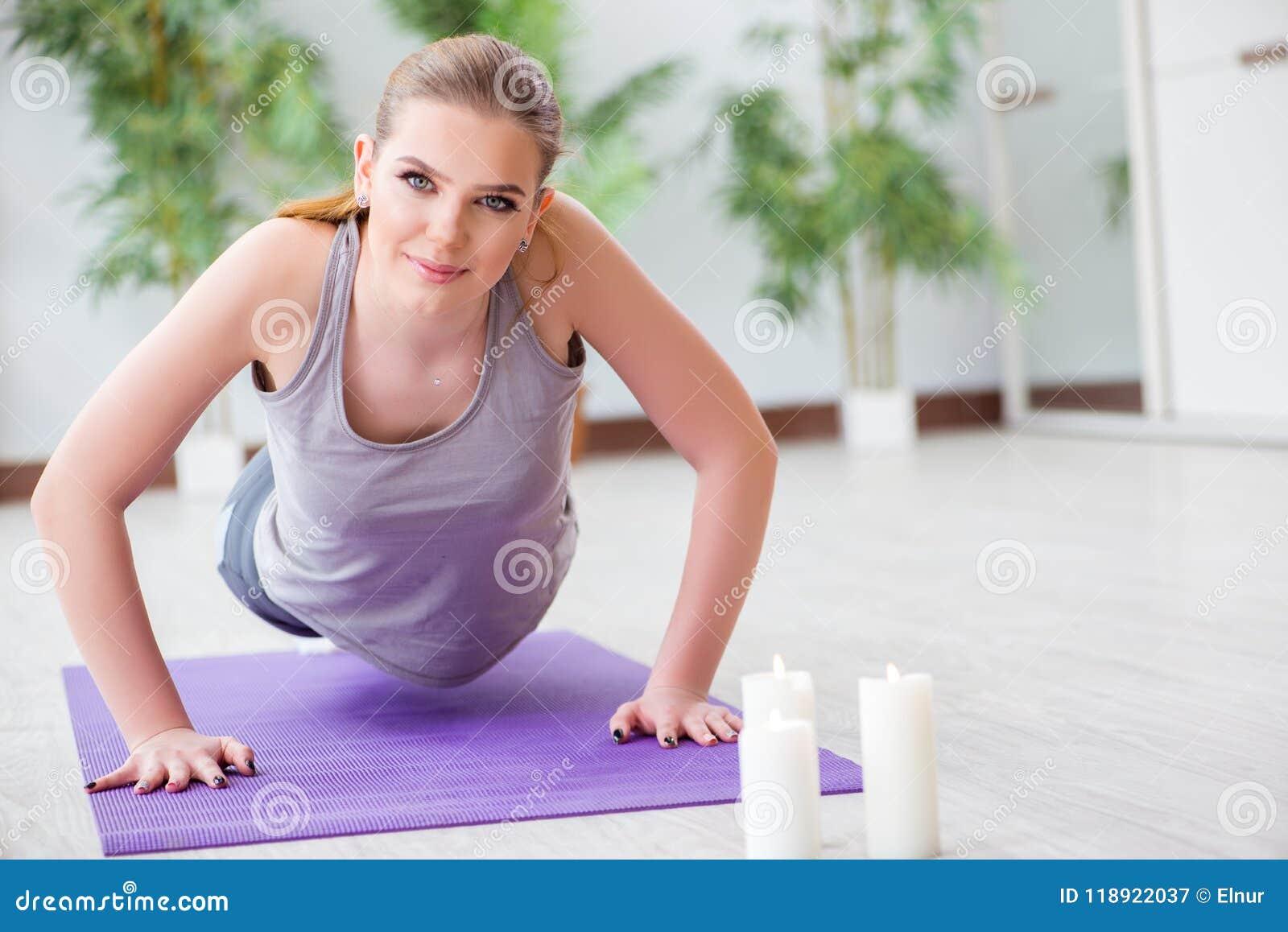 La mujer joven que ejercita en pasillo de deportes en concepto sano