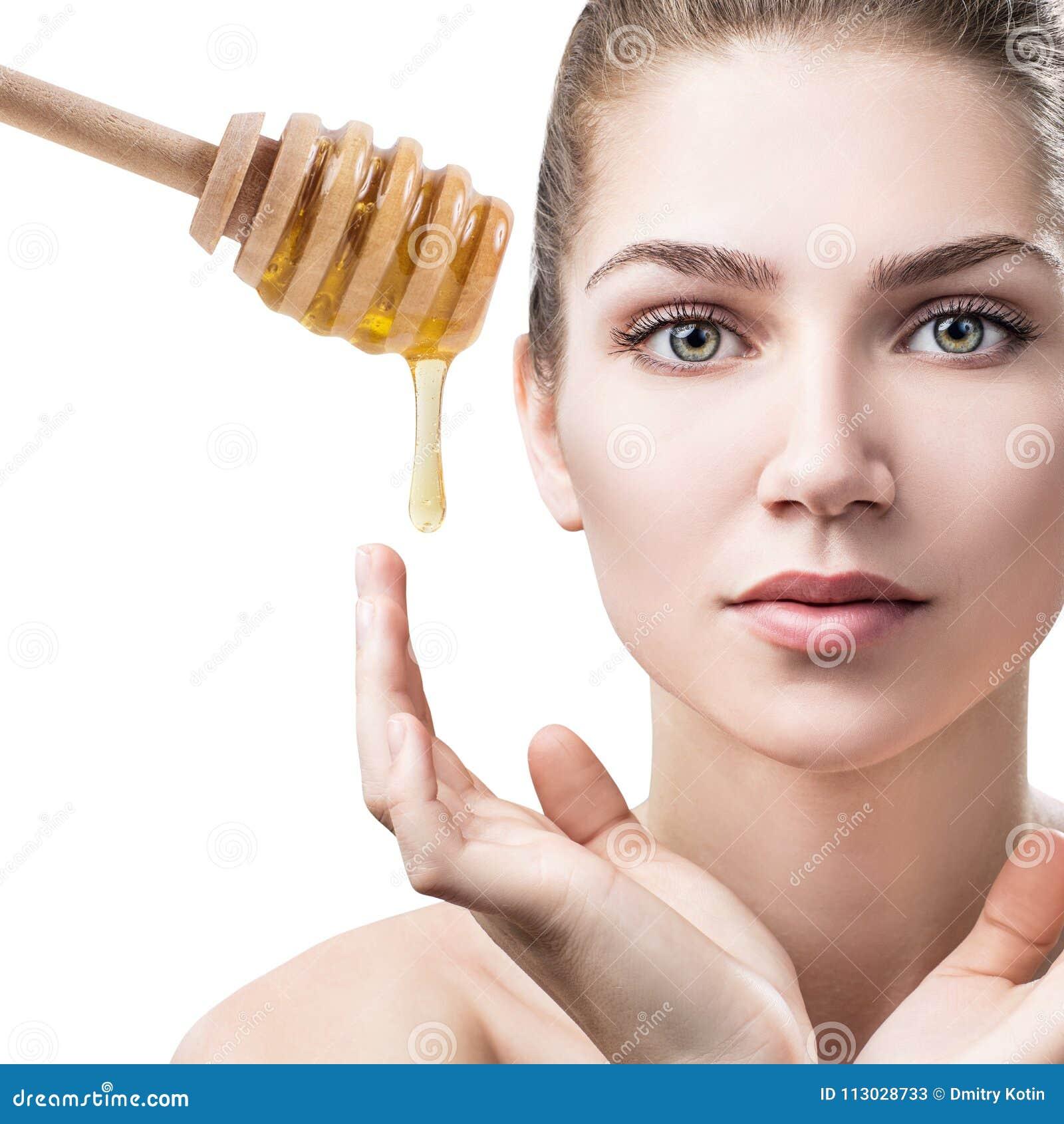La mujer joven se prepara para la máscara facial de la miel