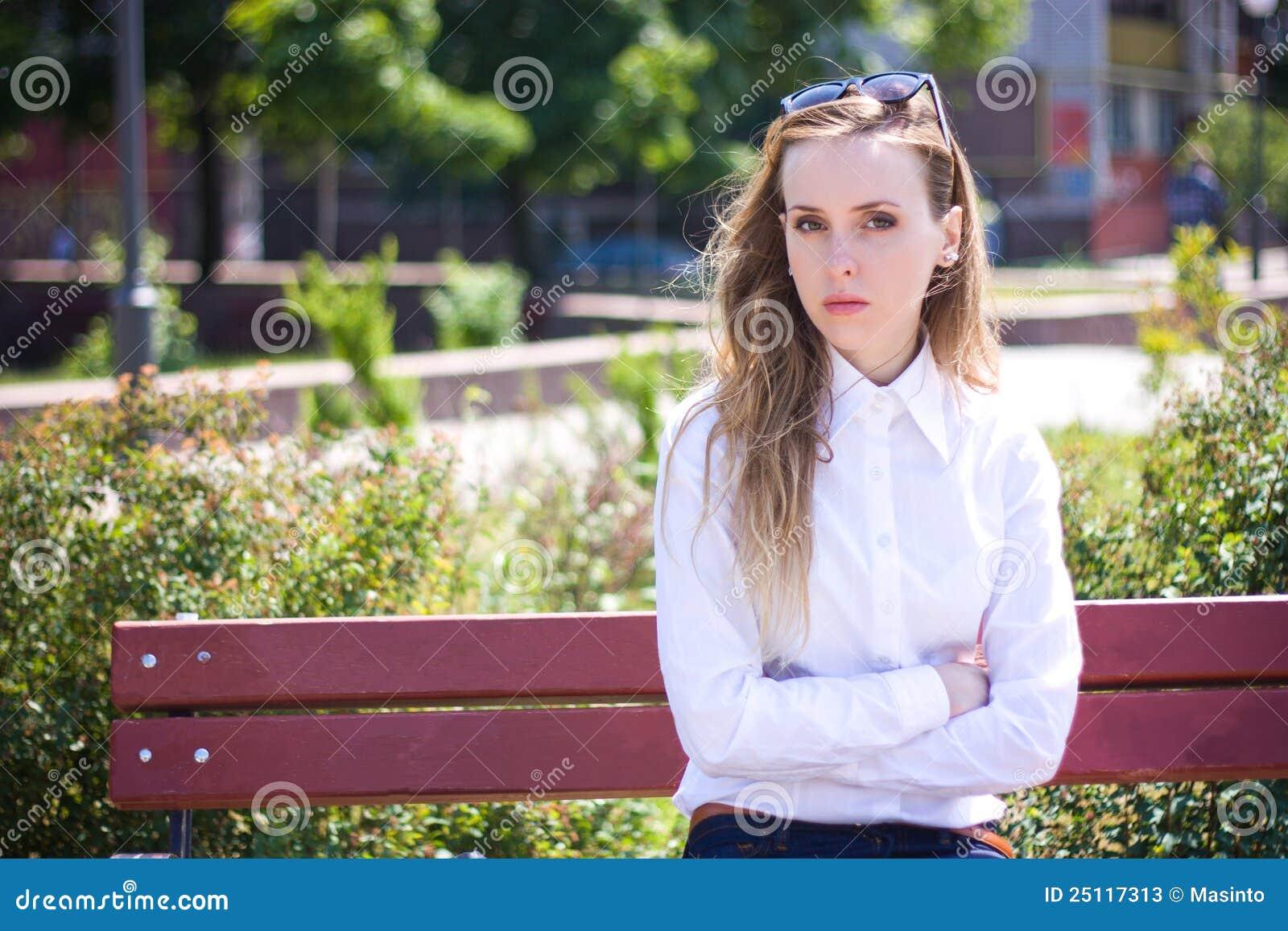 La mujer joven se sienta en el banco