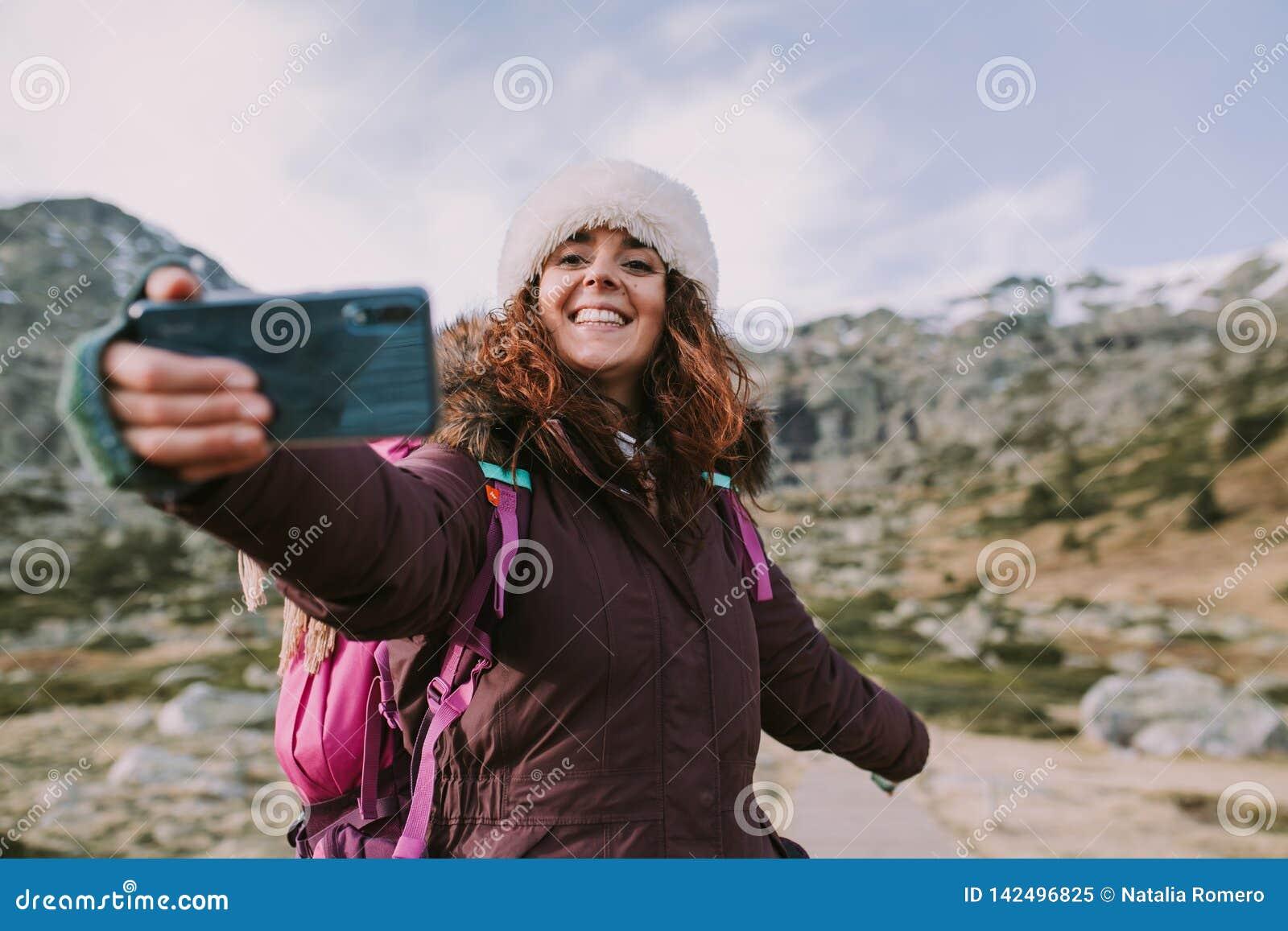 La mujer joven toma una fotografía en la montaña