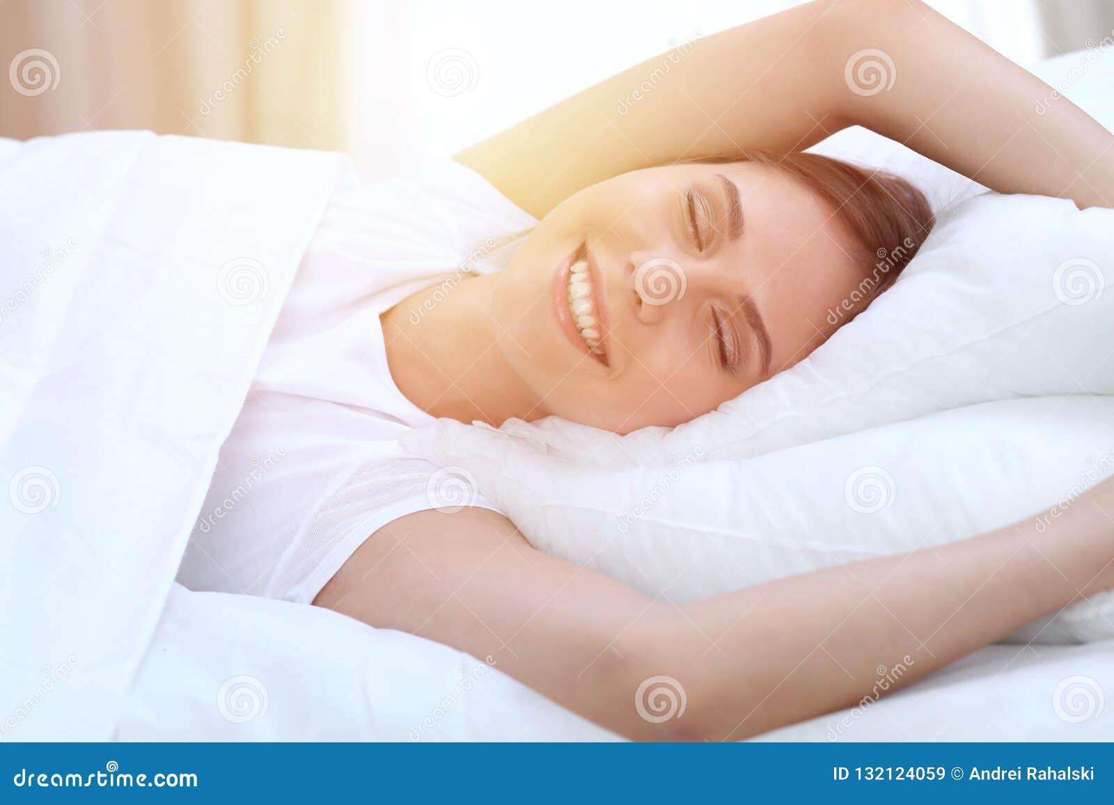 La mujer joven y feliz hermosa que estira las manos mientras que miente en cama comfortablemente y dichosamente sonríe antes desp
