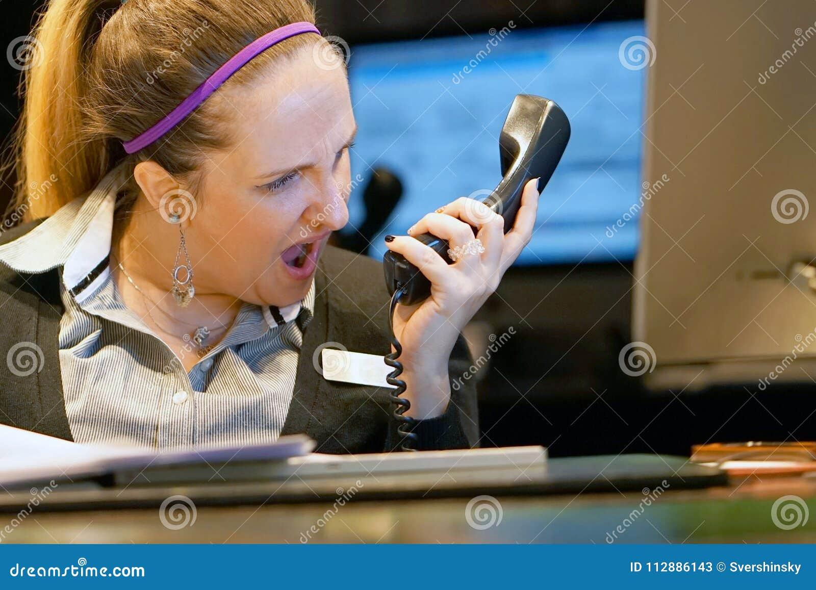 La mujer jura con el cliente por el teléfono