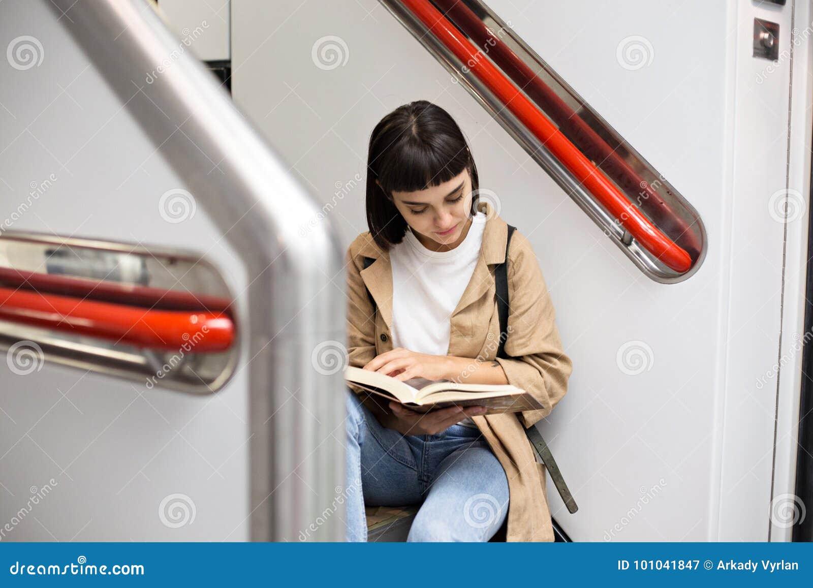 La mujer lee el libro en las escaleras del tren