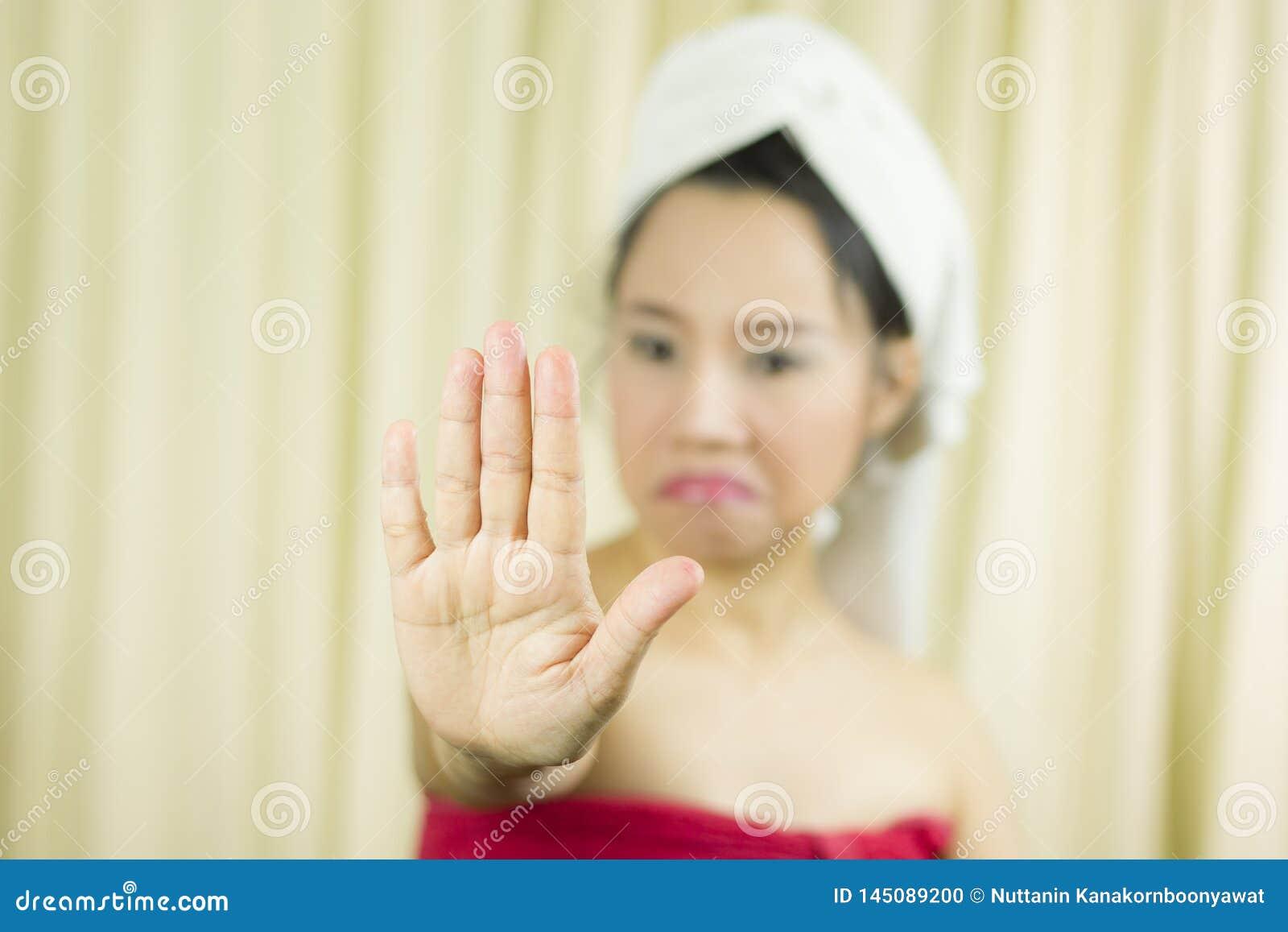 La mujer lleva una falda para cubrir su pecho despu?s del pelo del lavado, envuelto en toallas despu?s de ducha y dando la muestr