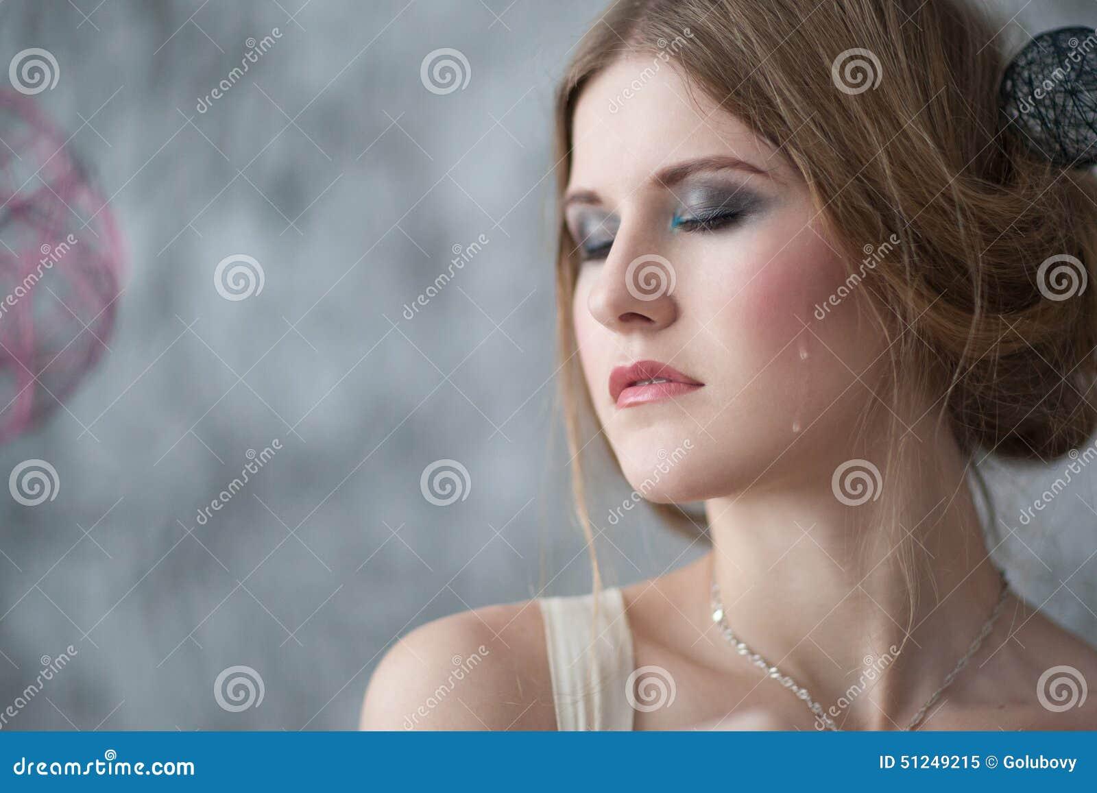 La mujer llora con los rasgones en una cara