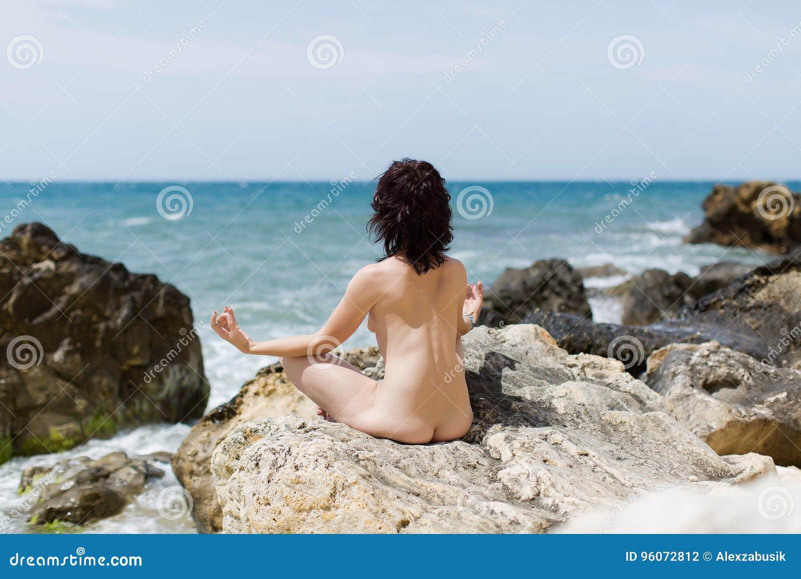 La Mujer Madura Desnuda Se Sienta En Roca En Día Ventoso Foto De