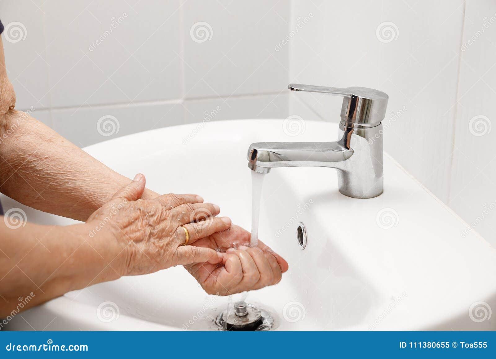 La mujer mayor lava la mano en cuarto de baño