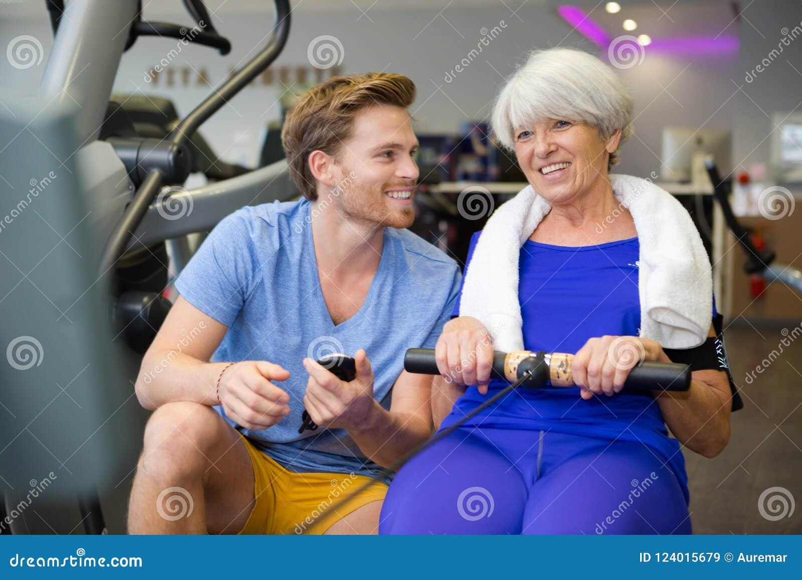 La mujer mayor que hace deporte ejercita con el coche o el instructor personal