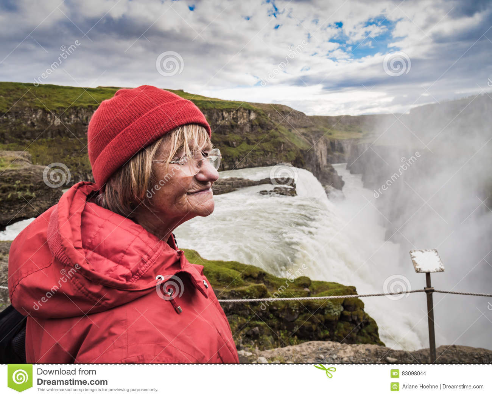 La Mujer Mayor Se Está Colocando En Una Cascada De Gullfoss