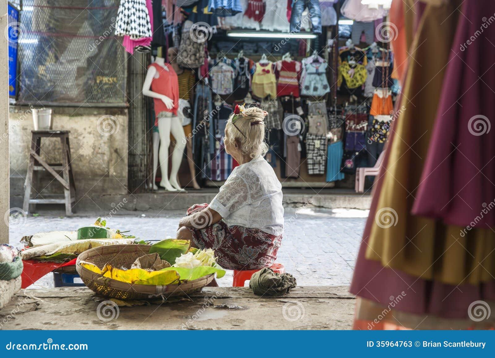 La mujer mayor sienta esperar para vender la producción.