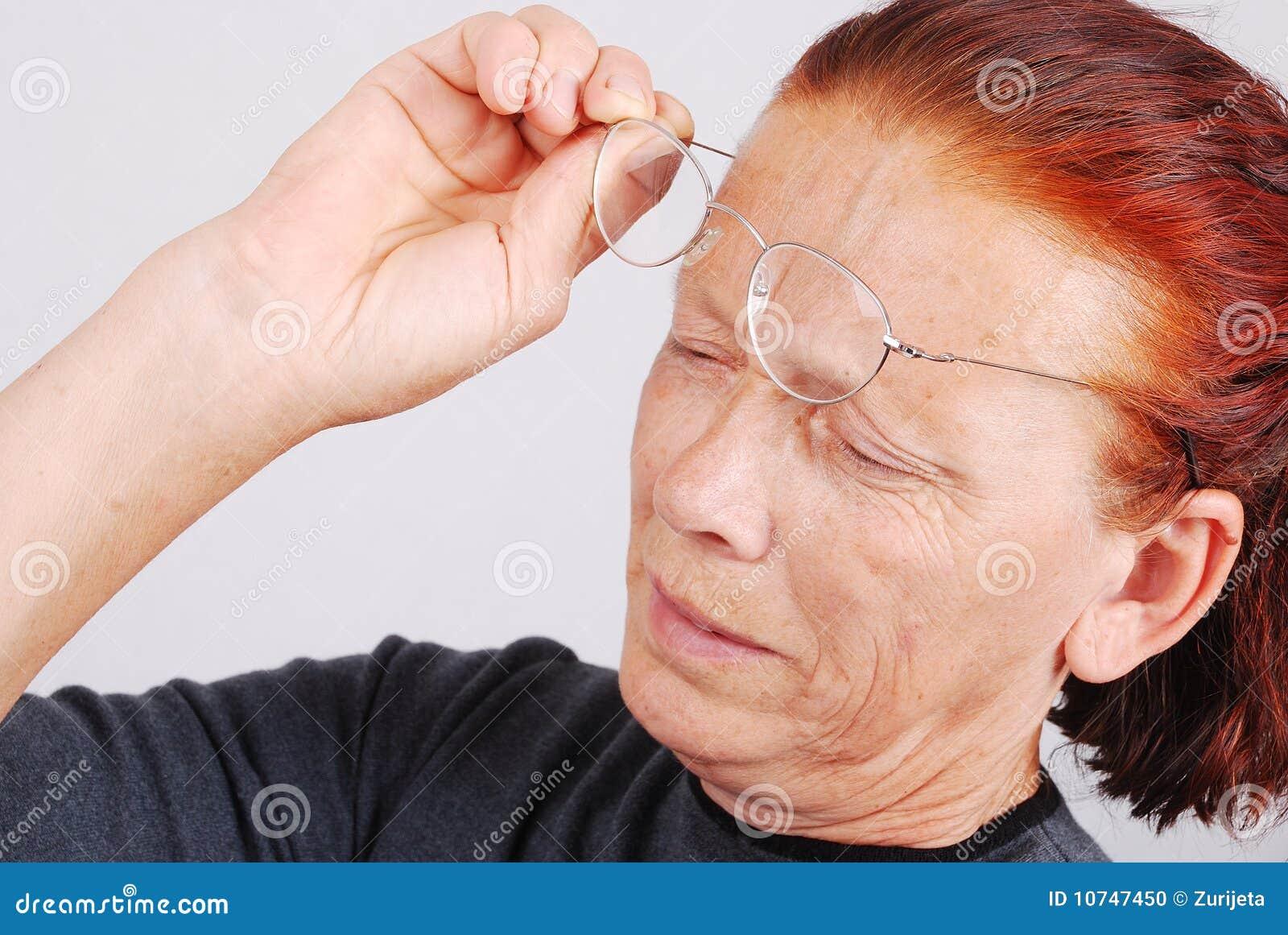 La mujer mayor tiene un problema con la vista, vidrios