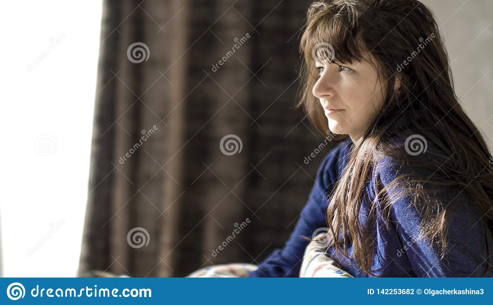 La mujer morena joven está sonriendo mientras que se sienta por la mañana en su cama