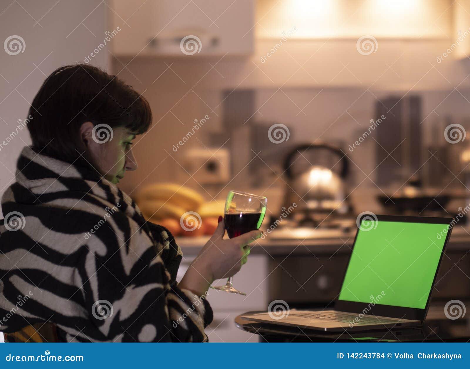 La mujer morena joven sostiene un vidrio de alcohol en su mano y miradas en la pantalla de un monitor del ordenador portátil, chr