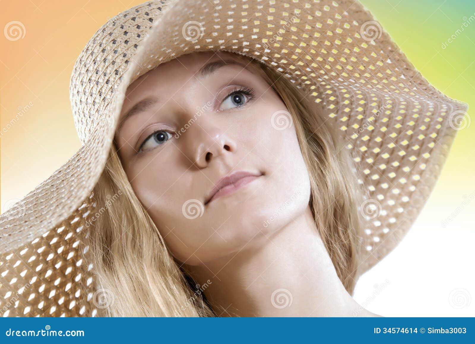 La mujer natural del pelo rubio de la belleza sin compone el sombrero de paja que lleva