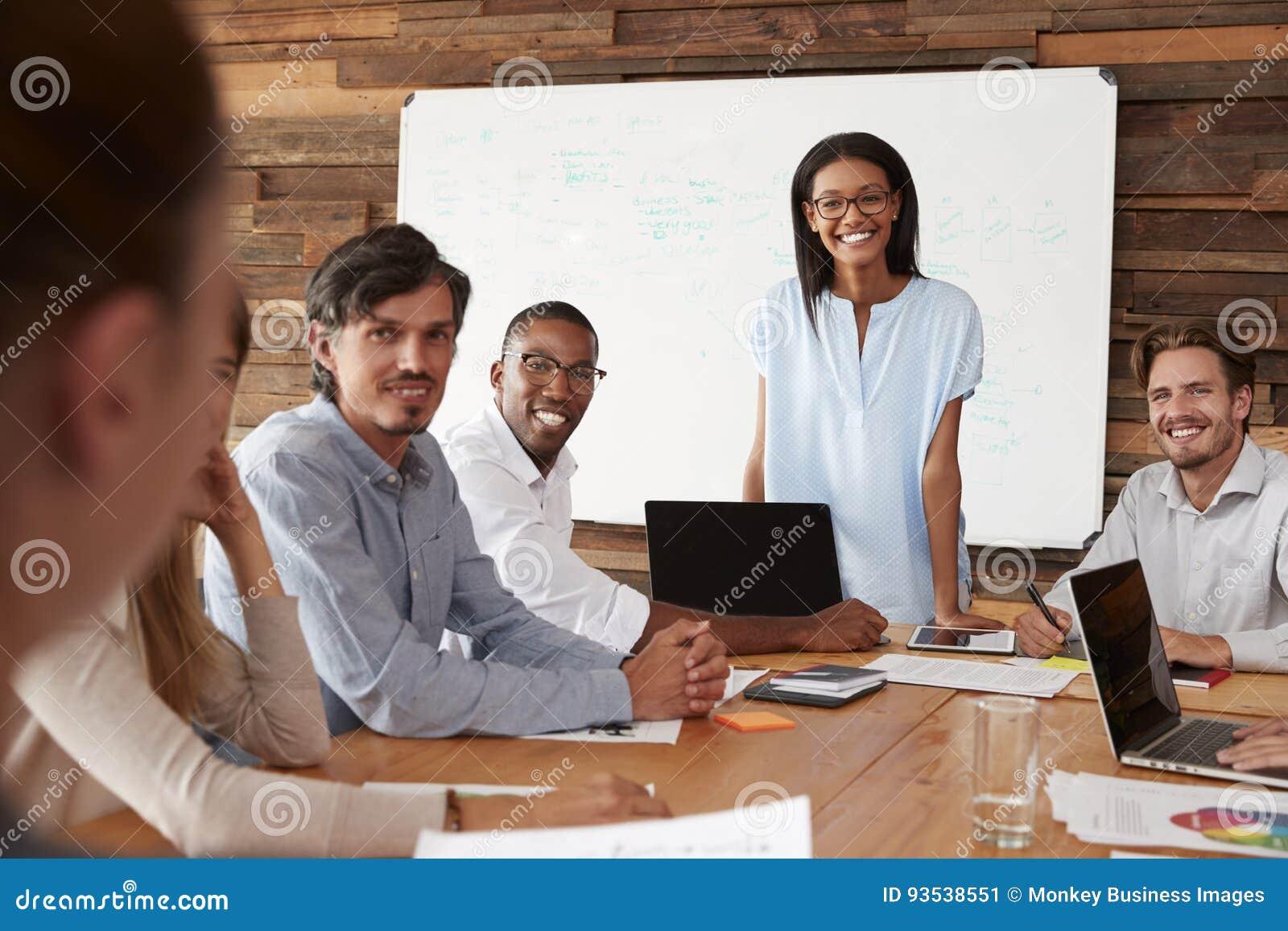 La mujer negra y los colegas jovenes en la reunión sonríen a la cámara