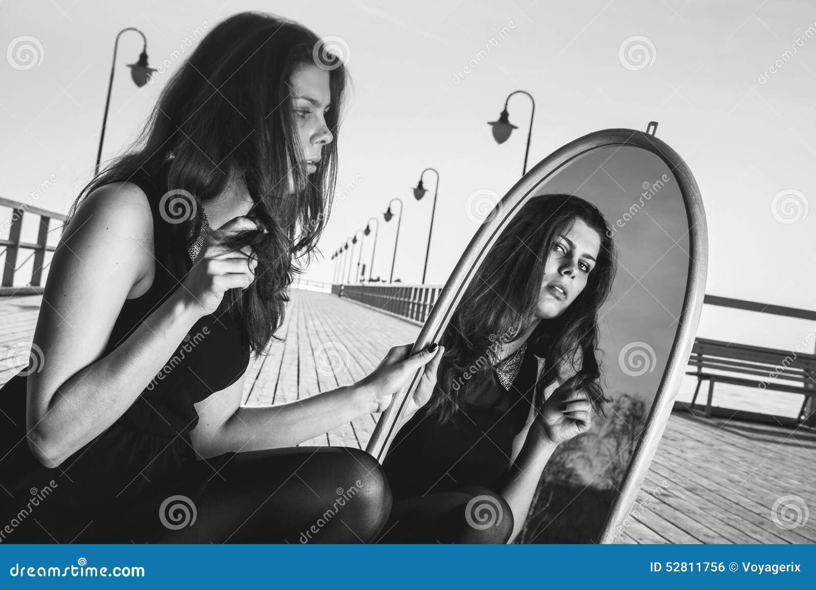 La mujer pensativa mira la reflexión en espejo
