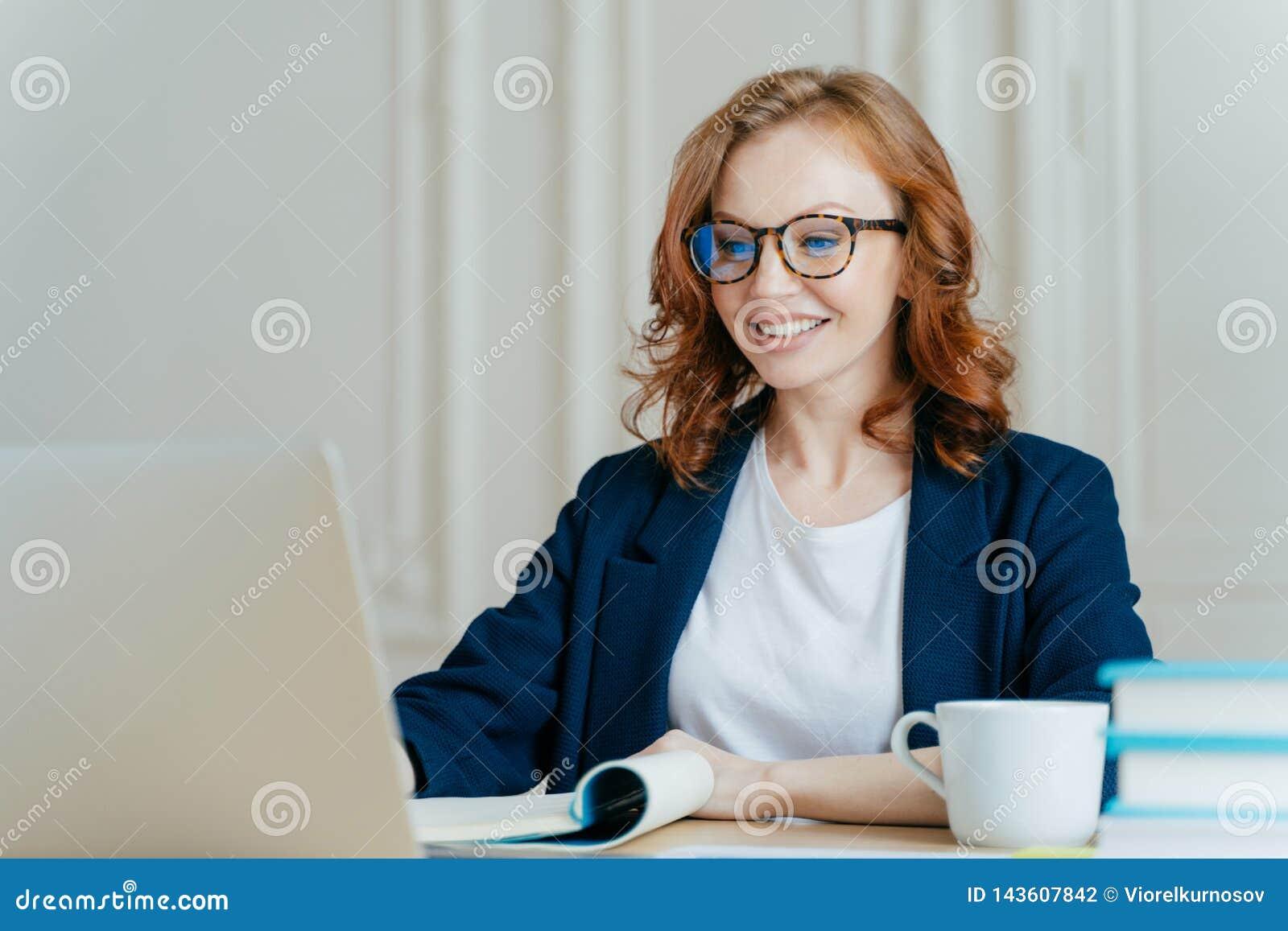 La mujer preciosa alegre tiene pelo del jengibre, sonrisa positiva, se sienta con el ordenador portátil en la mesa, feliz de hace