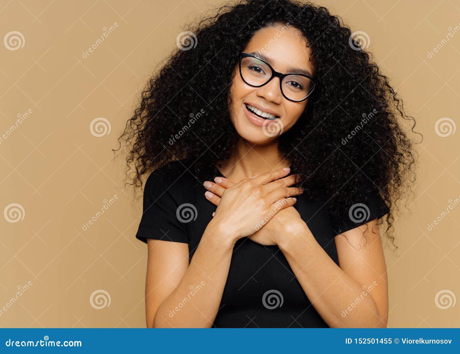 La mujer preciosa tocada con el peinado rizado, guarda las palmas en pecho, inclinaciones dirige, tiene sonrisa encantadora en ca